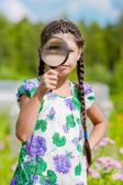 Smiling girl with magnifying glass — Stock Photo