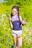 Girl with magnifying glass and book stays among flowers — Stock Photo