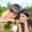 Boy an girl drink milk — Stock Photo