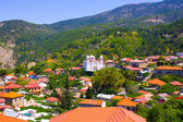Mountain Village Pedoulas, Cyprus. View over roofs of houses, mountains and Big church of Holy Cross — Stock Photo