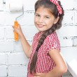 Stock Photo: Girl holding paint roller on brick wall