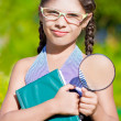 Stock Photo: Girl with magnifying glass and book