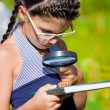 Stock Photo: Girl looking through magnifying glass on beetle