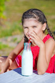 Girl drinking milk from bottle — Stock Photo