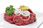 Minced meat with parsley, onions and egg on a plate — Stock Photo