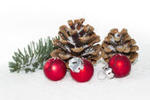 Red Christmas balls with pinecones, fir twig and snow — Stok fotoğraf