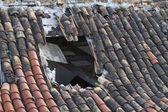 Old tiled roof with a large hole — Stock Photo