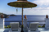 Sun beds under an umbrella in Greece with sea view — Stock Photo