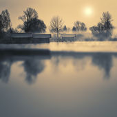 Boathouses on a lake in winter with fog and sun — Stock Photo