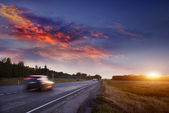 Car on the road at sunset — Stock Photo