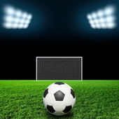 Soccer ball on grass against black background — Stock Photo
