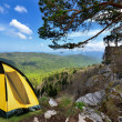 Yellow camping tent on a shore in a morning light - Stock Photo