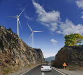 The road, windmills and mountains — Stock Photo