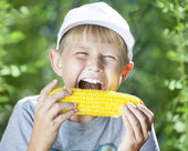 Boy and hot corn — Stock Photo
