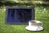 Tablet pc и выпить чашечку кофе на траве — Стоковое фото