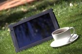 Black tablet pc and a cup of coffee — Stock Photo