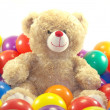 Teddy bear is playing with colorful balls — Stock Photo