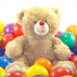 Teddy bear is sitting in colorful balls — Stock Photo