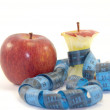 Whole apple and apple core with tape measure isolated — Stock Photo #24270433