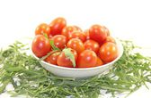 Delicious baby tomatoes and rocket in the plate isolated on white — Stock Photo