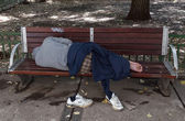 Sleeping homeless man on the bench — Photo
