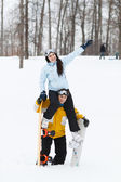 Young man and woman with treir snowboards — Stock Photo
