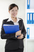 Business person standing and holding a document — Stock Photo