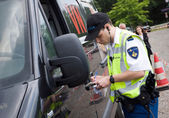 Policeman is checking driving license — Stock Photo