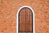 Деревянные двери на кирпичной стене. — Стоковое фото