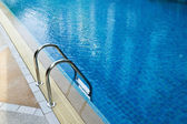 Grab bars ladder in swimming pool — Stok fotoğraf