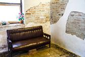 Eski tuğla duvarlar siyah kanepe. — Stok fotoğraf