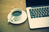 Black coffee in a white cup on a table with a computer. — Foto de Stock