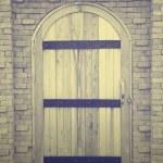 Old wooden door in brick wall — Stock Photo #50002699