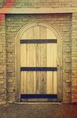 Antigua puerta de madera en pared de ladrillo — Foto de Stock