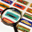 Stamps in an album and magnifying glass - Stock Photo