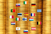 Flags of eurozone countries against piles of coins — Stock Photo