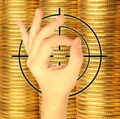 Hand and target against coins of yellow metal — Stock Photo