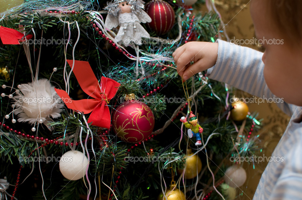 The child decorates a green New Year tree with color toys — Stock Photo #12374690