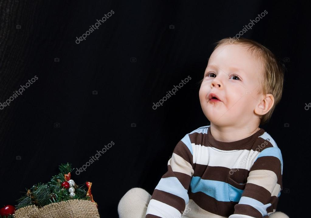 On a black background the boy in a striped sweater and a bag with toys sits — Stock Photo #12376121