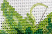 Cross stitching with a needle closeup — Stock Photo