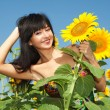 Stock Photo: Young woman in the field of sunflowers