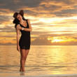 Fashion woman on the sea sunset background — Stock Photo