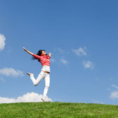 かなり若い女性の緑の草にジャンプ — ストック写真