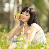 Cute woman eating the apple in the park with dandelions — Stock Photo
