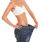 Pretty woman shows her weight loss by wearing an old jeans — Stock Photo