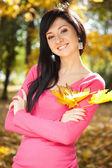 Jeune femme jolie, debout dans le parc en automne — Photo