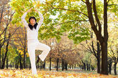Pretty woman doing yoga exercises in the autumn park — Stock Photo