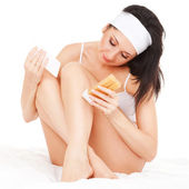 Cute woman depilating her legs — Stock Photo