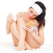 Cute woman depilating her legs — Stock Photo