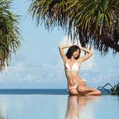 选址在海滩上游泳池旁边的年轻女人 — 图库照片